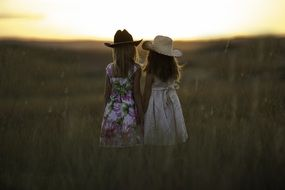 sisters in hats on the summer field