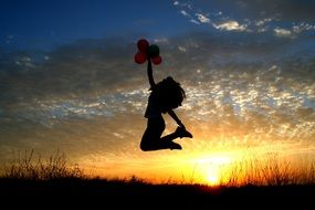 girl with balloons in hands jumped on the sunset background