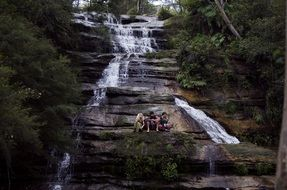 nature waterfall with persons relaxing