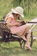 young girl in hat book summer day