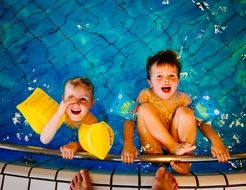 Two boys are swimming in the pool