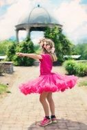 little girl dancing in a bright pink dress
