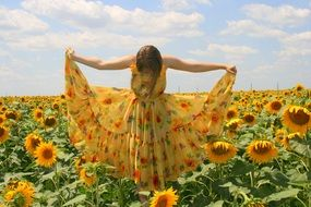 girl in a yellow dress on a field with sunflowers