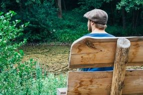 Rear view of a man who sits on a bench