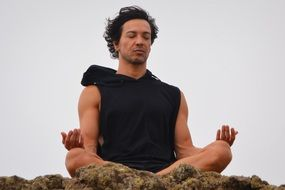 man relaxes through meditation