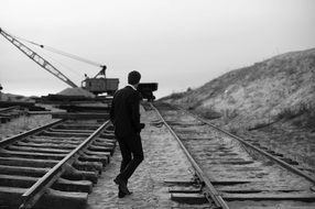 black and white photo of a young man in a suit on the railroad tracks