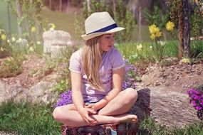 blond girl in the hat sitting in the garden