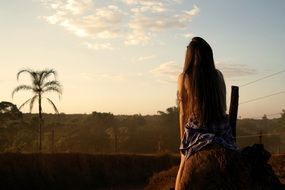 young woman with long hair admiring landscape