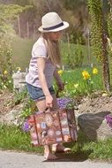 girl child in the hat barefoot toting luggage