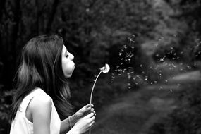 black and white photo of a girl with a dandelion