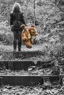 little girl with a teddy bear on the stairs