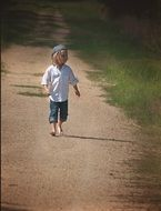 child walks on a dirt road
