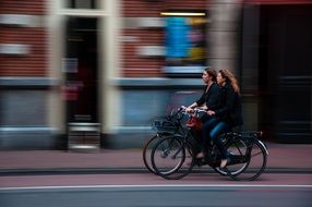 girls on bicycles ride down the street
