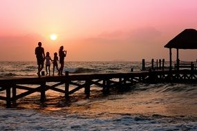 family on a pier over pink sunset background