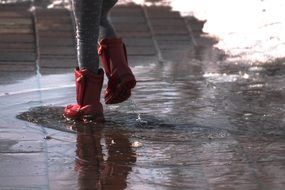 Human in a boots walking on a puddles