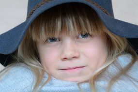 blonde girl face in hat blue eye