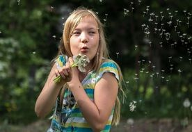 photo of the girl is blowing a dandelion