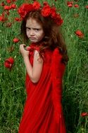 Little girl in wreaths of poppies on a poppy field