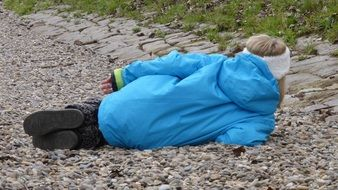 child girl lays on her side on pebbles, back view