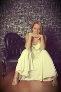 girl in a wedding dress sitting on a leather chair
