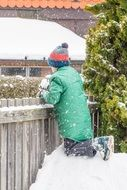 the child is sitting on a pile of snow near the fence