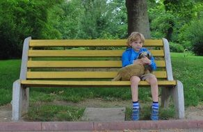 little boy with a dog on a park bench
