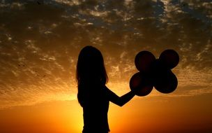 shadowed silhouette of a girl with balloons in hands on sunset background