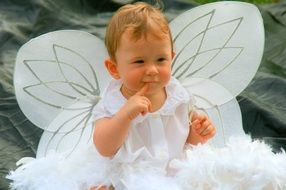 a toddler in a white angel costume with wings