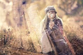 picture of the girl is blowing a dandelion