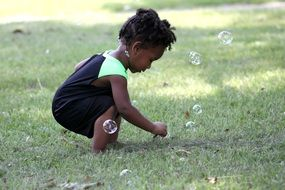 black girl plays with soap bubbles in the garden