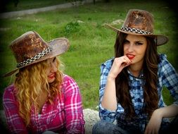two girls is sitting in a cowboy hat