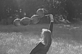 Black and white photo of girl playing with a balloons