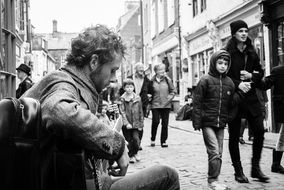 Black and white image of a street musician among people