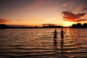 children stand in the water and watch the sunset