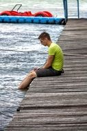 a young man sits on the edge of a wooden pier