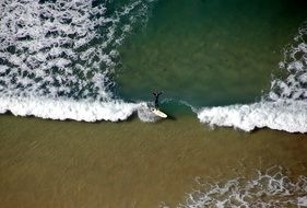 surfer in the wave of a bird's eye view