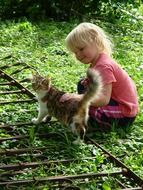 girl is playing with a kitten in the garden