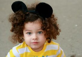 blue-eyed child with curly hair with a headdress of ears of Mickey Mouse