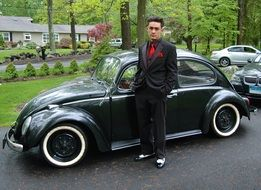 young man near a classic car