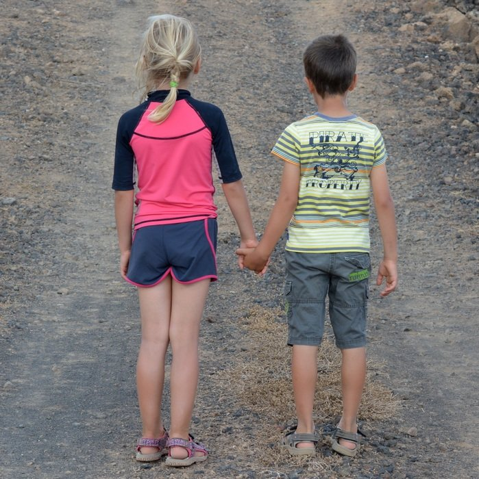 View from behind of children holding hands