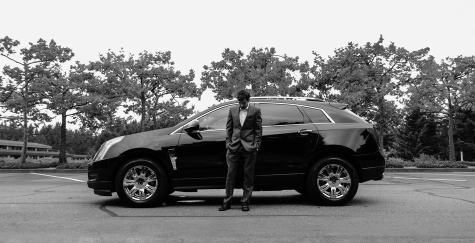 a man in a suit near a black car