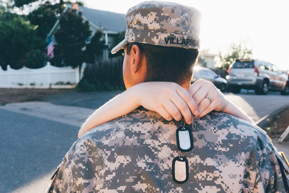 girl embracing man in military clothes