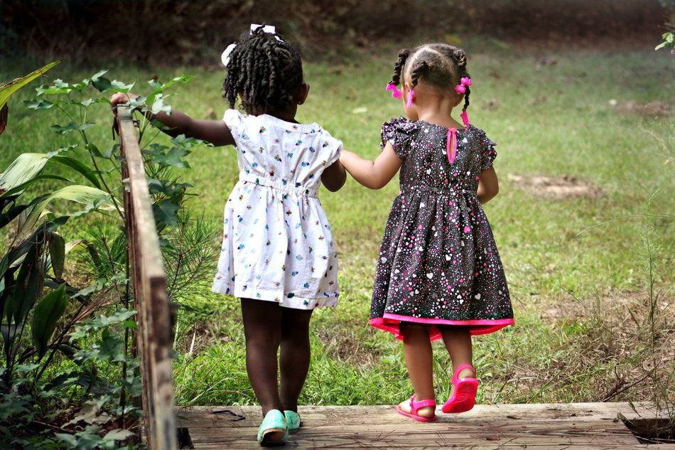 Rear view of little girls who hold hands