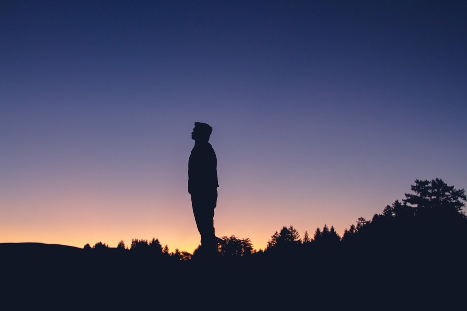 silhouette of a young man at dusk