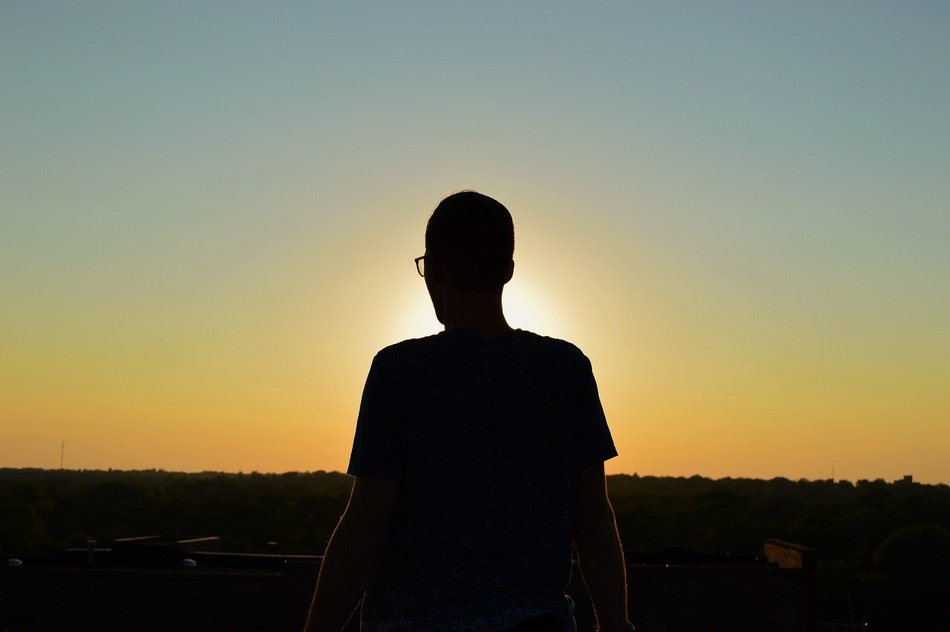 dark male silhouette at sunset sky