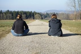 girlfriends sitting on path road forest view