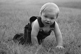 Black and white photo of baby crawling on a grass