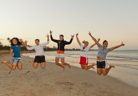 happy young girls jumping on beach, usa, puerto rico