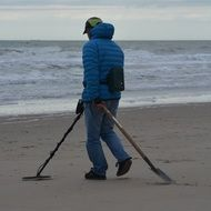 young man with a metal detector and shovel