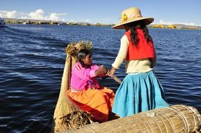 two child girls in traditional boat on titicaca lake